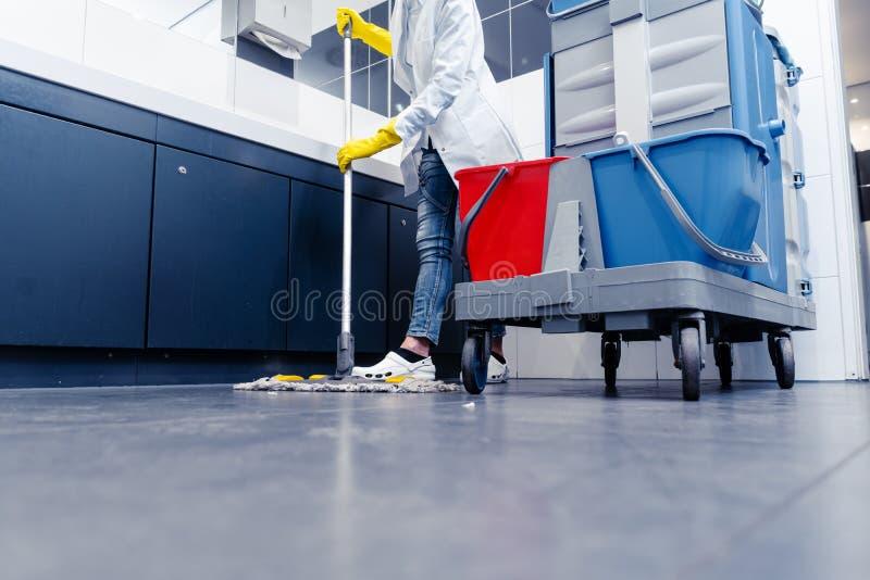 Laag schot die van schoonmaakster de vloer in toilet dweilen royalty-vrije stock foto