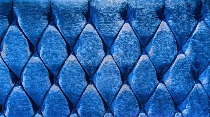 Laag-type fluweelscreed met knopen wordt aangehaald die Blauwe gewatteerde de stofferingsachtergrond van Chesterfield stijl dicht stock fotografie