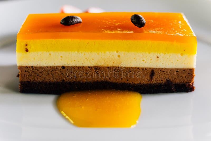 Laagcake met inbegrip van oranje saus en chocoladebovenste laagje met koffiezaad en gediend met verse gesneden aardbei royalty-vrije stock afbeelding