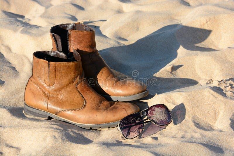 Laarzen en zonnebril in zand stock afbeelding