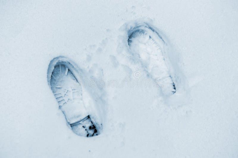 Laarzenvoetafdruk en voetstap op de sneeuwoppervlakte, wintertijd F royalty-vrije stock afbeelding
