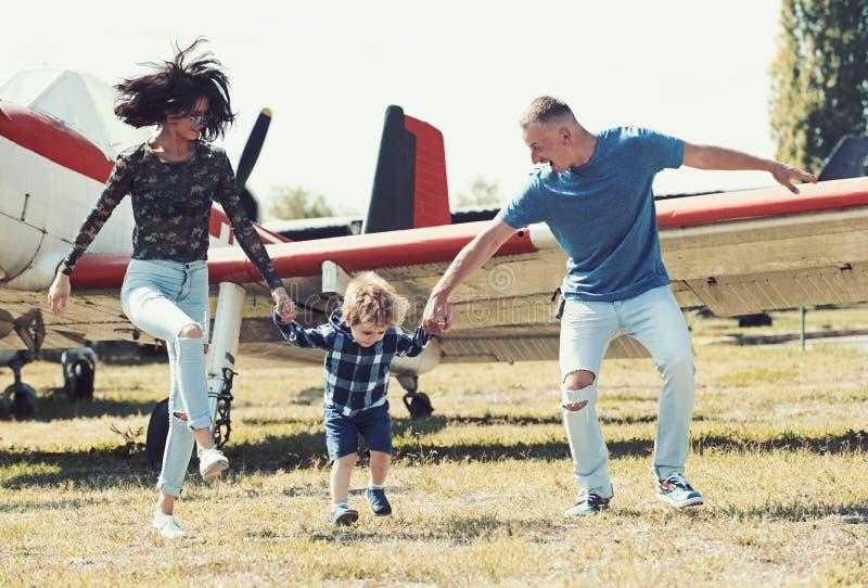 Laat begin onze reis Het reizen door de lucht Familie op vakantiereis Paar met jongenskind bij vliegtuig Vliegtuigenreis en royalty-vrije stock foto