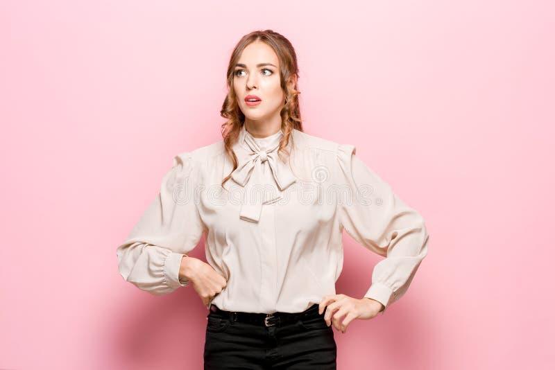 Laat me denken Twijfelachtige peinzende vrouw met nadenkende uitdrukking die keus maken tegen roze achtergrond stock afbeelding