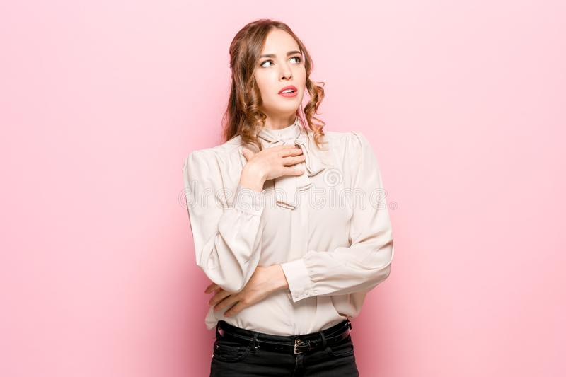 Laat me denken Twijfelachtige peinzende vrouw met nadenkende uitdrukking die keus maken tegen roze achtergrond royalty-vrije stock fotografie
