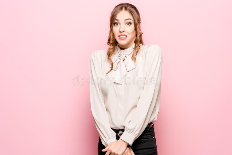 Laat me denken Twijfelachtige peinzende vrouw met nadenkende uitdrukking die keus maken tegen roze achtergrond royalty-vrije stock foto