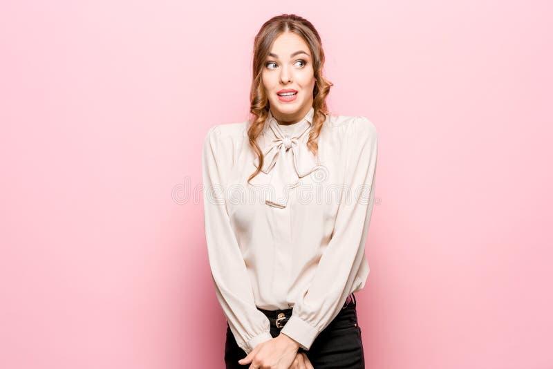 Laat me denken Twijfelachtige peinzende vrouw met nadenkende uitdrukking die keus maken tegen roze achtergrond stock afbeeldingen