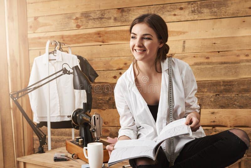 Laat me u mijn nieuw project tonen Gelukkige creatieve vrouwelijke kleermakerszitting op lijst en holdings het naaien regelingen, stock afbeelding