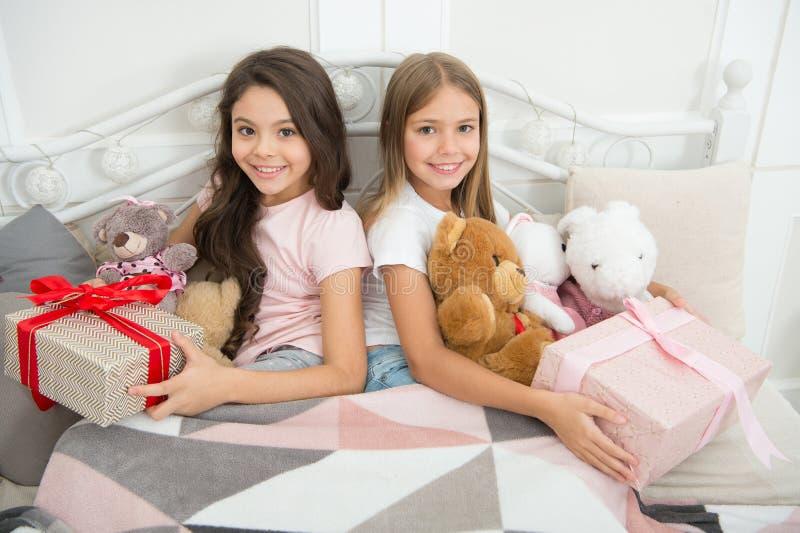 Laat open Kerstmisgiften Ontspannen de zusters beste vrienden met speelgoed in bed met giftdozen Vrolijke Kerstmis en vrolijk stock foto