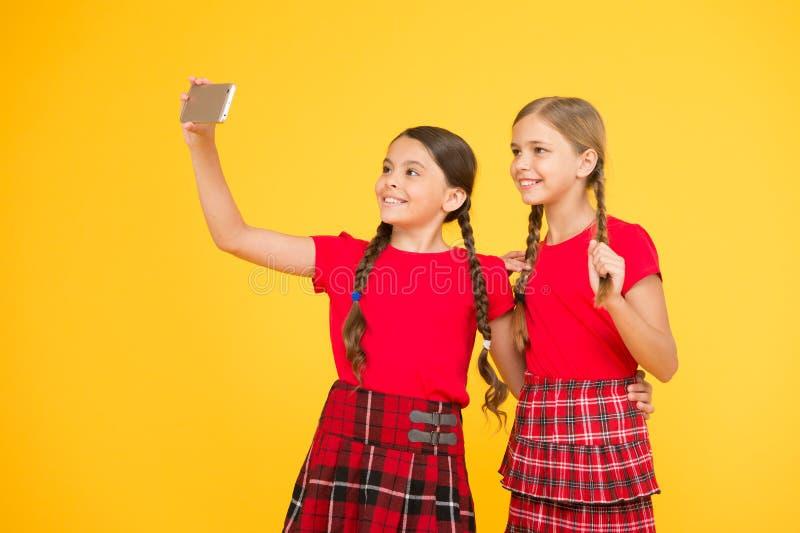 Laat pic maken Meisjes in eenvormig kleine meisjes die selfie op telefoon maken Het hebben van pret zusterschap en vriendschap ge stock foto's