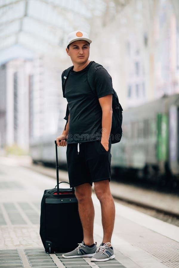Laat reis beginnen Reiziger met koffer wachtend vervoer aan luchthavenstation Klaar te reizen Draag reiszak Mens stock foto's