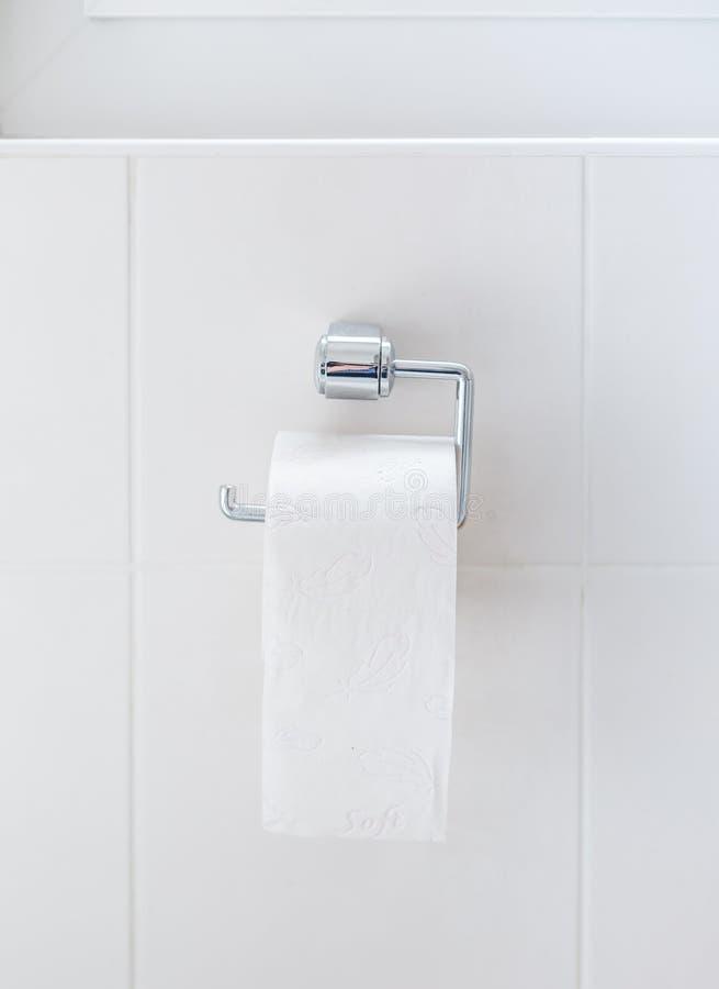 Laatste rol toiletpapier hangen op de houder stock afbeelding