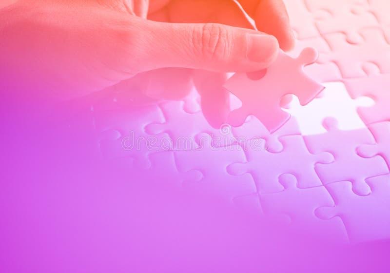 Laatste stuk van witte duidelijke figuurzaagholding met de hand, stap van succesconcept, ultraviolet stock fotografie