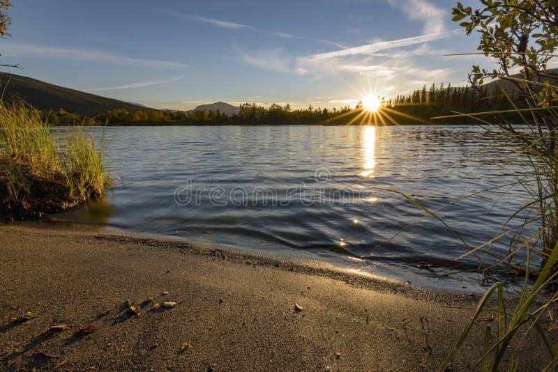 Laatste zonnestralen tijdens rustige zonsondergang over kalm meer, Zweden stock foto
