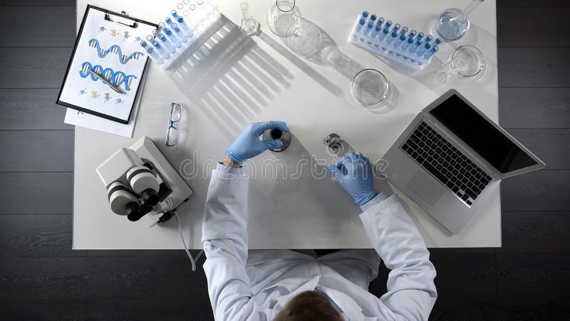 Lab assistant checking oil product in flask, making chemical mixture, top view stock photography