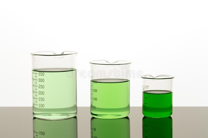 Lab equipment. Three beakers of different size with green liquid.  royalty free stock photos