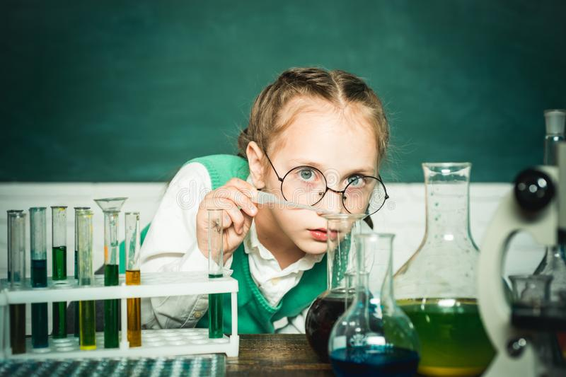 Lab microscope and testing tubes. My chemistry experiment. Back to school and happy time. Cheerful smiling little boy. Having fun against blue wall stock photo