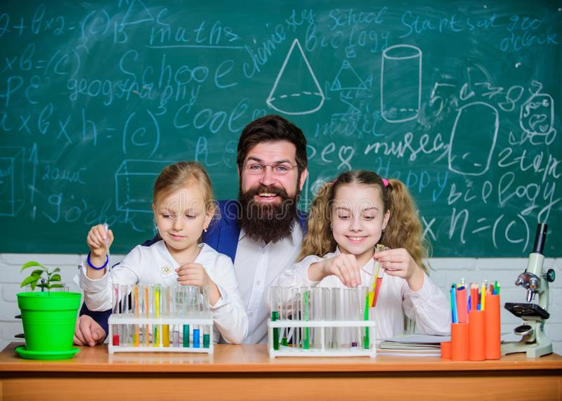 In lab. Small girls holding test tubes in school laboratory. Little pupils and teacher doing laboratory research royalty free stock image