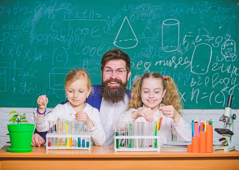 In lab. Small girls holding test tubes in school laboratory. Little pupils and teacher doing laboratory research. Children performing tests with laboratory stock image