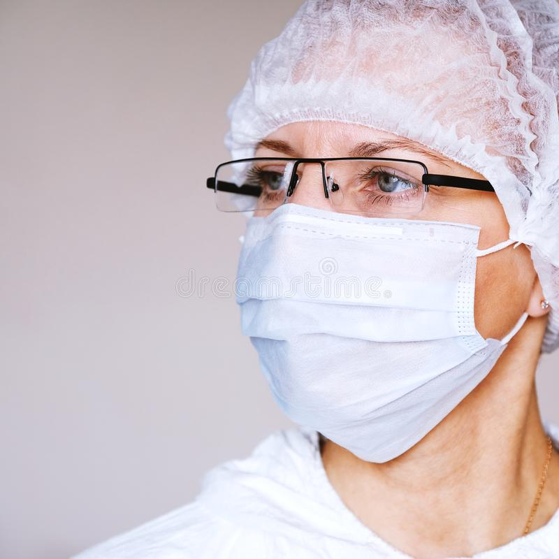 Lab technician, medic. Jar for analysis. On the face of a protective mask. Glasses. Protective suit. stock photo