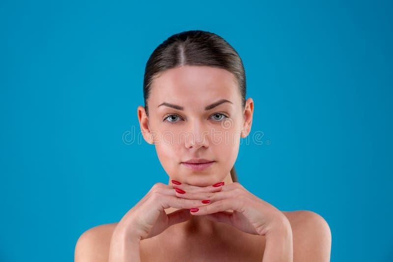 Labbra del primo piano e spalle di giovane donna caucasica con trucco naturale, pelle perfetta e gli occhi azzurri sul blu immagini stock