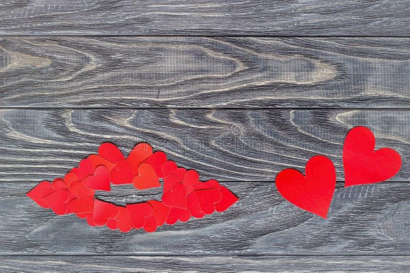 Labbra di piccoli cuori rossi su un fondo di legno Il concetto di fotografia stock libera da diritti
