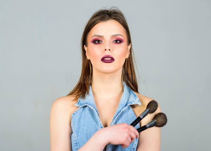 Labbra scure di trucco Donna attraente che applica la spazzola di trucco Rifornimenti professionali di trucco Imperfezioni nascon fotografie stock libere da diritti
