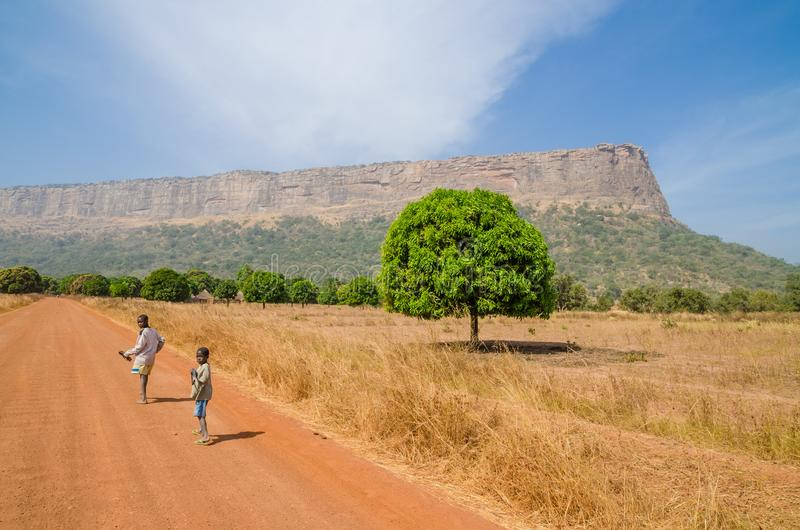 Labe,几内亚- 2013年12月20日:走在土路的两个未认出的男孩回顾与树和山 免版税库存照片