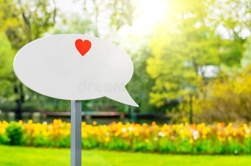 Label blanc pour les mots au coeur en parc au printemps et été images stock