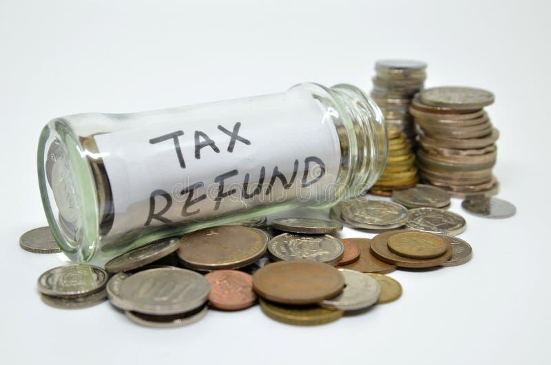 Label de remboursement d'impôt fiscal dans un pot en verre avec des pièces de monnaie se renversant  image stock