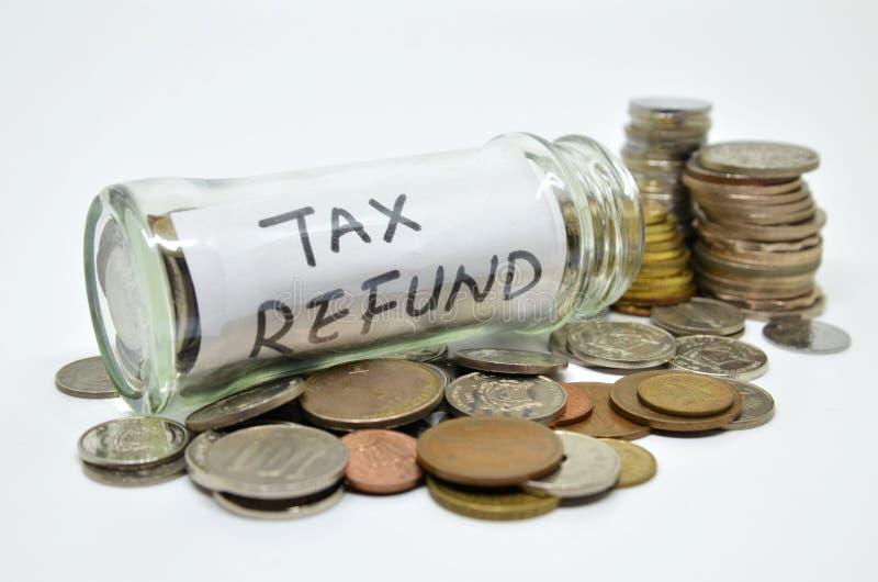 Label de remboursement d'impôt fiscal dans un pot en verre avec des pièces de monnaie se renversant  photo stock