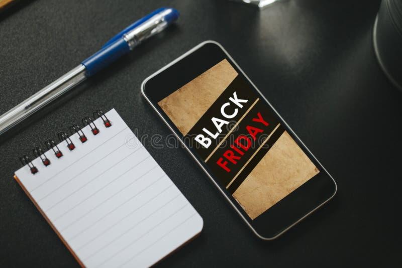 Label de vente de Black Friday dans un écran de téléphone portable au-dessus d'une table noire d'affaires image libre de droits