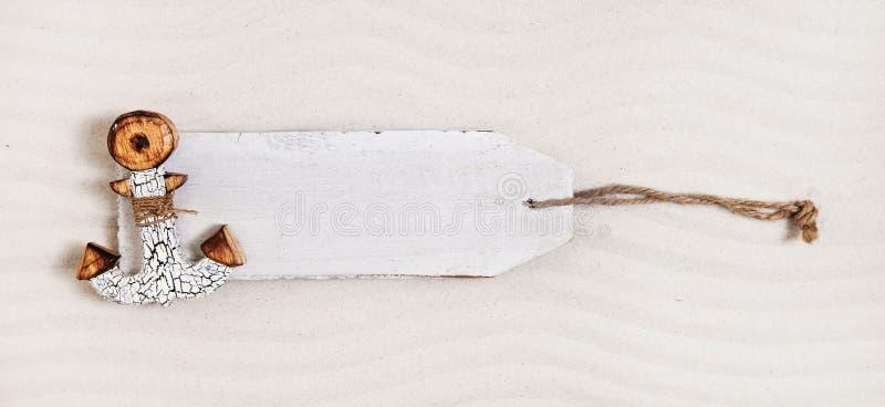 Label en bois blanc avec une ancre dans le sable La publicité du panneau image stock