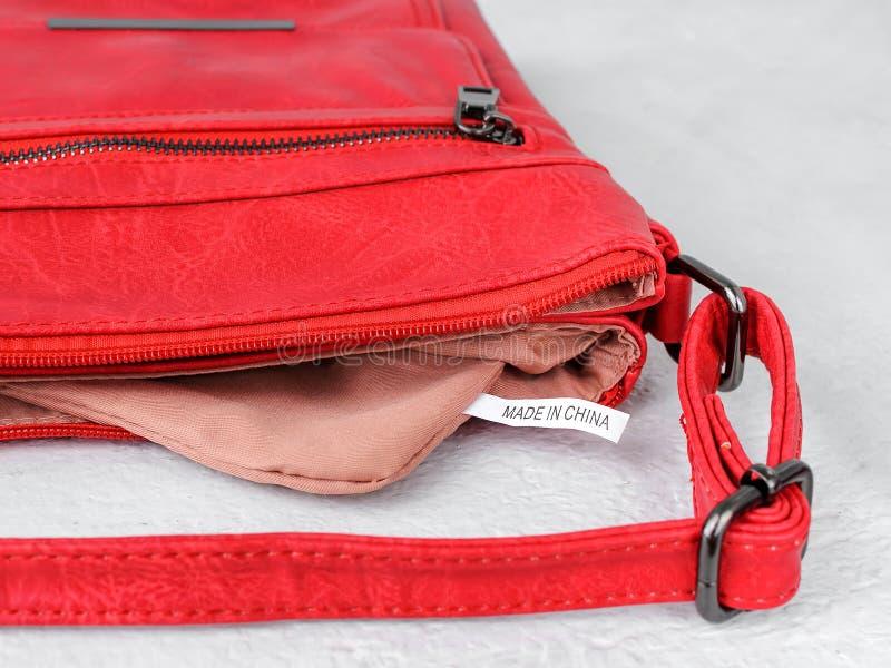 Label fabriqué en Chine à l'intérieur d'un petit sac à main occasionnel rouge avec une longue poignée et une attache de fermeture photo libre de droits