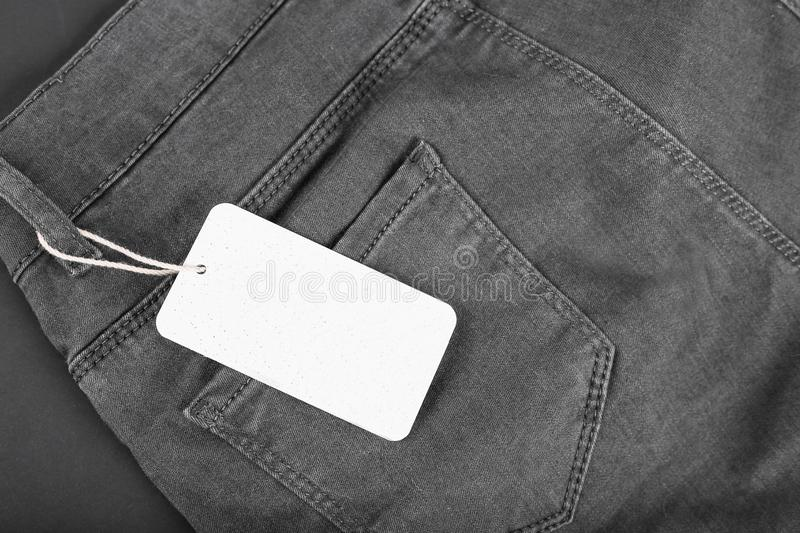 Label price tag mockup on black jeans on black background. Label price tag mockup on black jeans stock photography