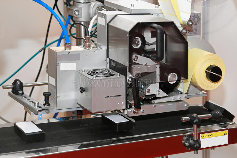 Labeller. Label printer and applicator machine at conveyer belt royalty free stock images
