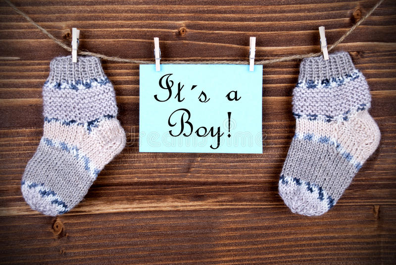 Label Saying It Is A Boy. A Light Blue Label With The Words It Is A Boy On It Hanging On A Line With Baby Socks stock photo