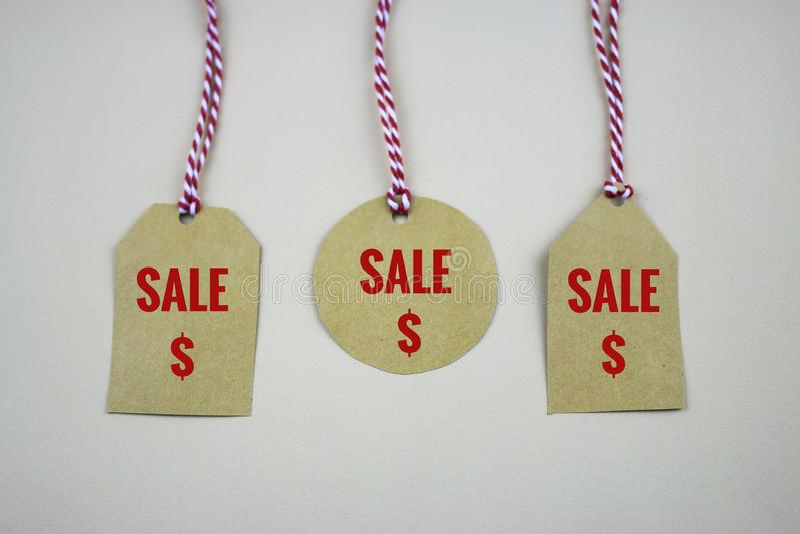 Labels accrochants d'étiquettes de vente sur la table blanche image stock