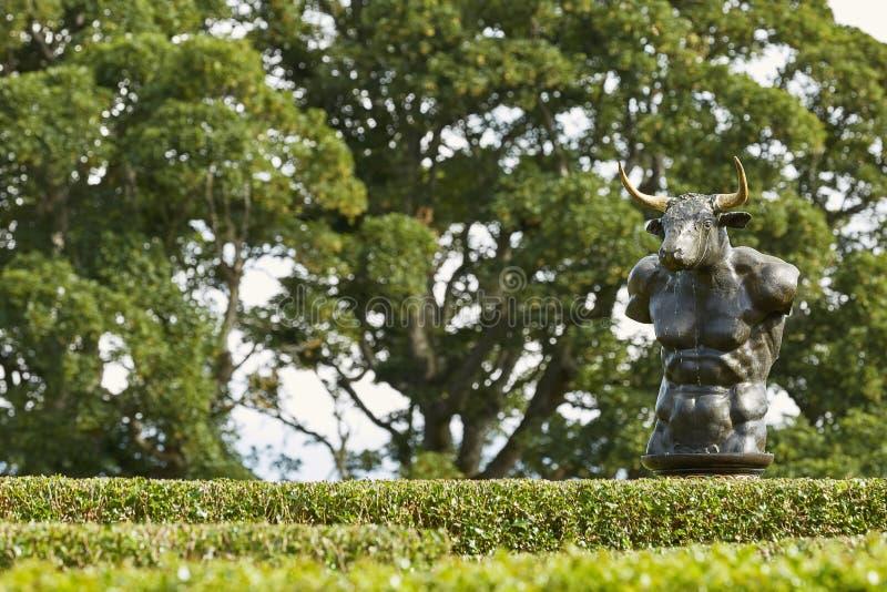 Laberinto del laberinto de los setos del acebo en el jard?n emparedado del castillo de Cawdor con la escultura de bronce del mino fotografía de archivo libre de regalías