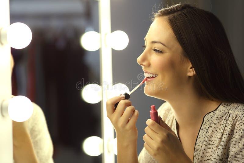 Labios de la pintura de la muchacha con un lápiz labial brillante fotos de archivo
