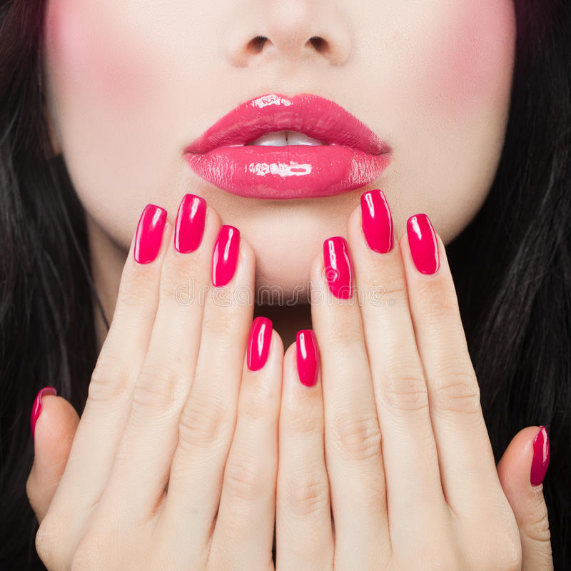 Labios del maquillaje con el lápiz labial rosado, Lipgloss y la manicura fotos de archivo