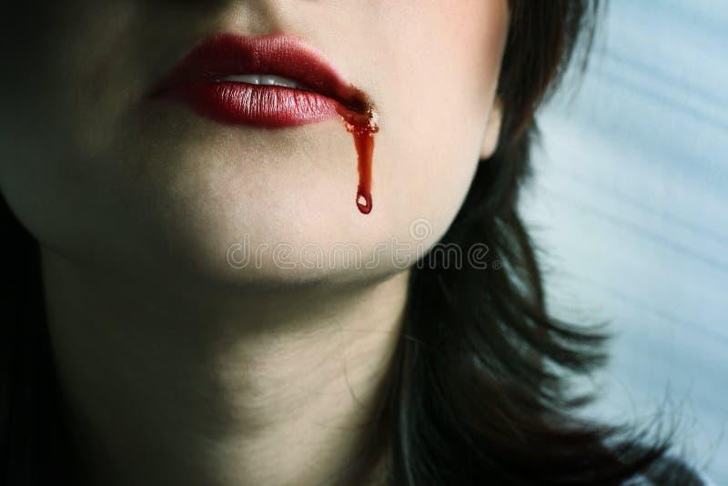Labios rojos con la sangre que cae cerca imagen de archivo