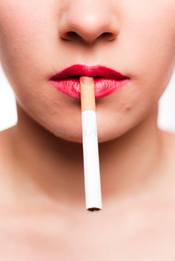 Labios rojos con un cigarrillo imagen de archivo libre de regalías
