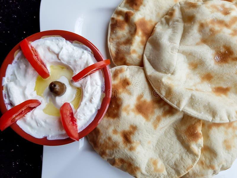 Labneh en tomaten Hoogste mening van een kom labneh, heerlijke en romige yoghurtonderdompeling met vlak brood Het voedsel van het royalty-vrije stock afbeeldingen