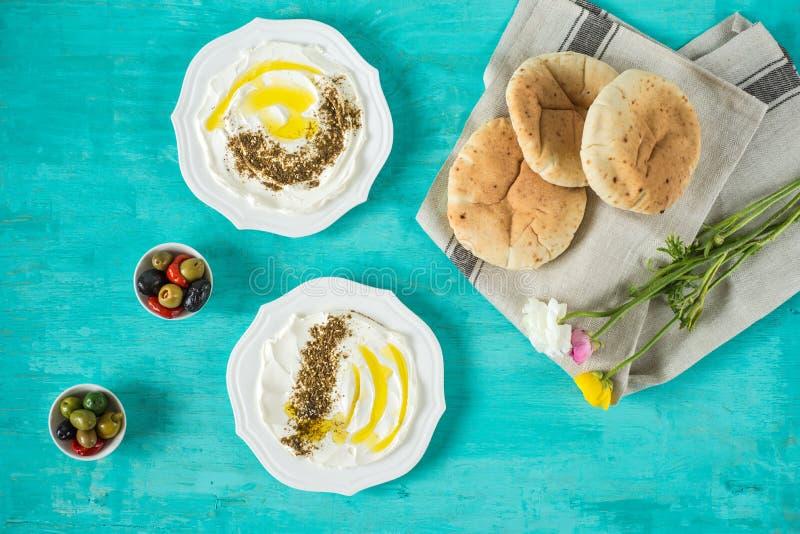 Labneh labanehmiddle wschodniej miękkiej kózki dojny ser z oliwą z oliwek, za «atar, cytryna, pita chleb, słuzyć przy tradycyjnym obrazy stock