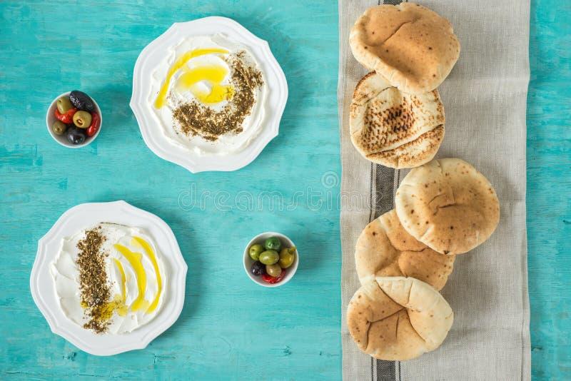 Labneh labanehmiddle wschodniej miękkiej kózki dojny ser z oliwą z oliwek, za «atar, cytryna, pita chleb, słuzyć przy tradycyjnym zdjęcie royalty free