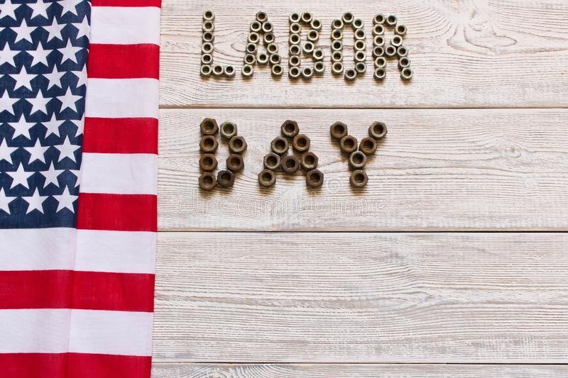Labor day. American flag and Inscription labor day on a light wooden background stock images