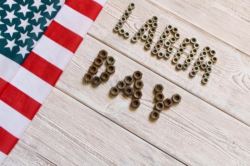 Labor day. American flag and Inscription labor day on a light wooden background royalty free stock image