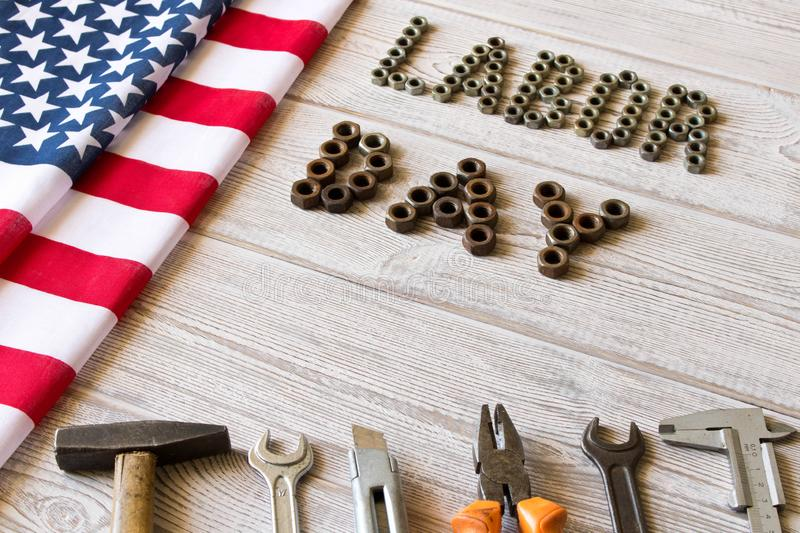 Labor day. American flag and Inscription labor day and various tools on a light wooden background royalty free stock images