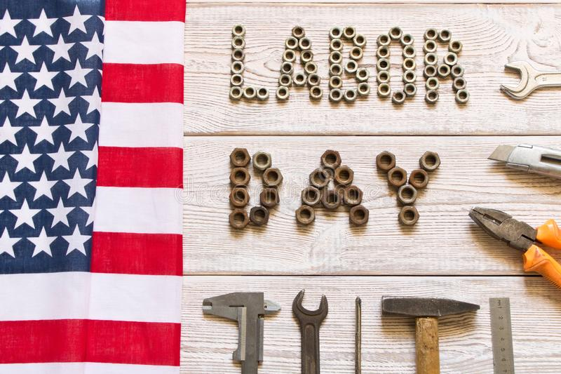 Labor day. American flag and Inscription labor day and various tools on a light wooden background royalty free stock photo