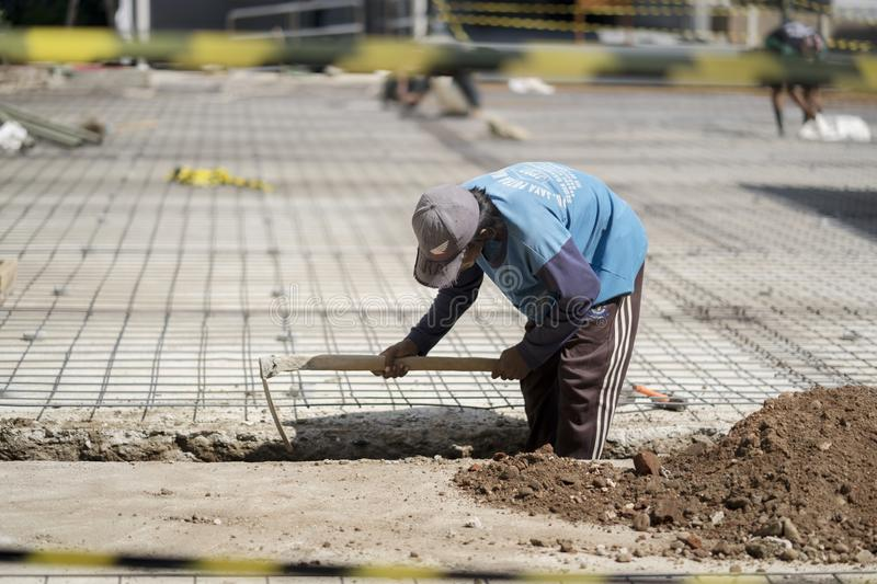 Labor worker digs the ground to make foundation stock image